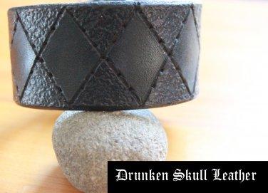 Dark green leather cuff with hand tooled argyle design