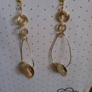 Gold cowry shell hoop style earrings with swirls.