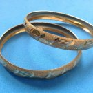 PAIR OF TWO YELLOW GOLD TONE SHINY, TEXTURED AND CUT DESIGN BANGLE BRACELETS