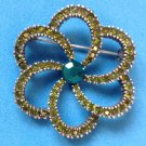 "Green rhinestone flower pin 1 3/4"" in diameter."