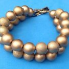 """Lucite double strand bracelet. Gold colored,textured & satin finish 8 1/"""" long."""