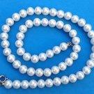 Classic white faux pearl single strand necklace.