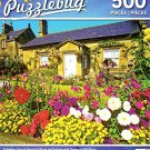 A Summer View of Denwick Village and Gardens with Flowers in Full Bloom - 500 Piece