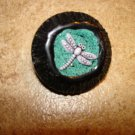 Black hard plastic button with dragonfly.