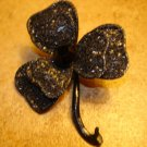 Large clover like metal button with black stone.