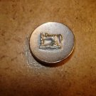 Old gold metal button with silver metal sewing machine.