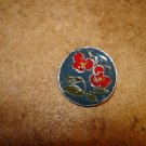 Signed silver metal button with red flower.