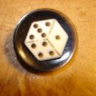 Black plastic button with dice.
