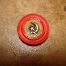 Red plastic button with silver metal moon and star.