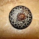 Carved black plastic button with brass sun.