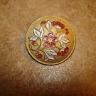 Gold metal button with red flowers and ivy.