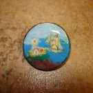 Large painted plastic button with lighthouse and sailboat.