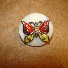 Mother of pearl button with metal butterfly.