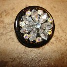 Hard plastic button with tier shape glass beads and rhinestones.
