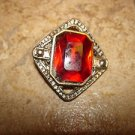 Silver metal button with large garnet color stone.