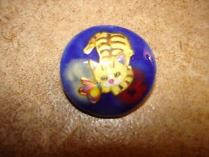 Blue plastic button with cat playing with butterfly.