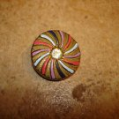 Metal button with pin wheel patern and rhinestone.