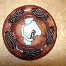 Large brown plastic button with braded rope.