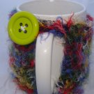 Fuzzy multi-colored mug koozie with button