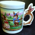 Easter Coffee Mug with Bunny Shaped Handle - Bunny kids playing on fence - EUC!