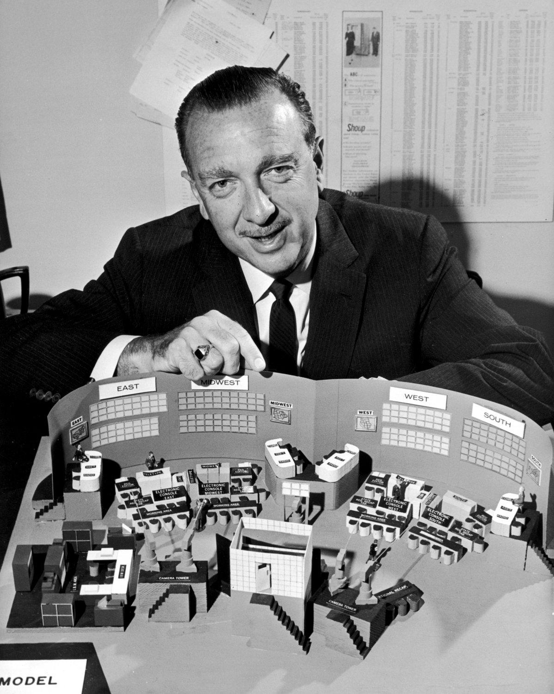 WALTER CRONKITE POSES W/ A CBS NEWS 1962 ELECTION HEADQUARTERS MODEL - 8X10 PUBLICITY PHOTO (AZ-048)