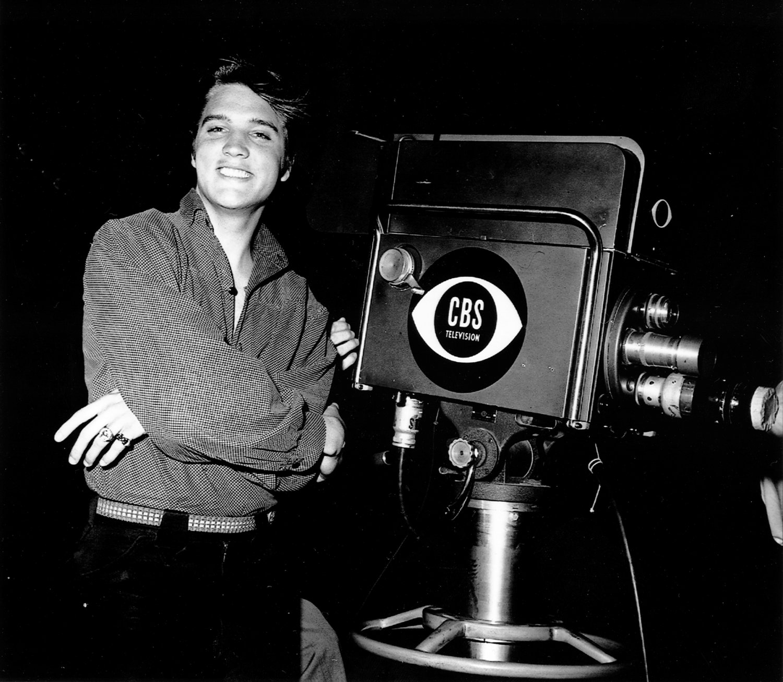 ELVIS PRESLEY NEXT TO TV CAMERA IN CBS STUDIO - 8X10 PUBLICITY PHOTO (EP-272)