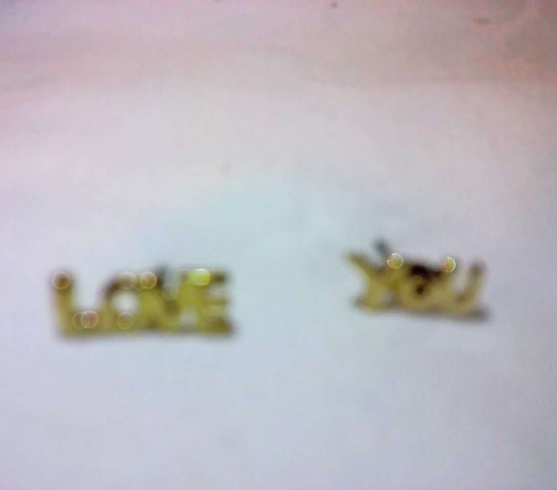Antique style gold stud earrings one reads 'love' and the other reads 'you'