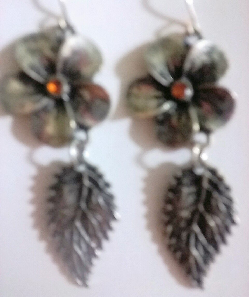 Antique style silver dangle earrings with a leaf charm attached to a flower.