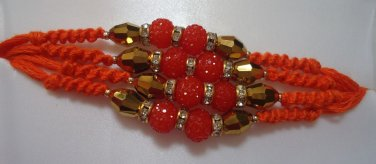 Coral Rakhi With Gold Tone Crystal Clear Stones By Teknowear