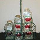SET OF THREE GLASS BOTTLESCHERRIES CRUET VINEGAR IN WIRE RACK