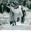 Tyrone Power carrying woman on film set. - 8x10 photo
