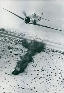 A fighter plane over the explosion. - 8x10 photo