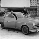 Gilbert Bécaud stepping into car,smiling. - 8x10 photo