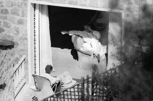 Katharine Hepburn relaxing on balcony. - 8x10 photo