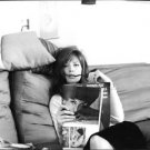 Monica Vitti reading magazine in sofa. - 8x10 photo