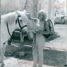 Sylvie Vartan pampering a horse. - 8x10 photo