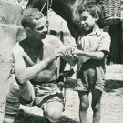 World War II. Soldier gives candy to Sicilian child - 8x10 photo