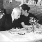 Charlie Chaplin listening to his wife Oona. - 8x10 photo