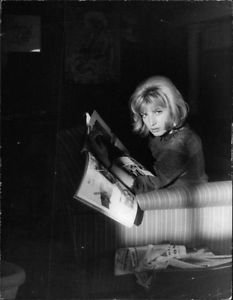 Monica Vitti looking up from magazine. - 8x10 photo