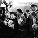 Judy Garland with flowers, surrounded by people. - 8x10 photo