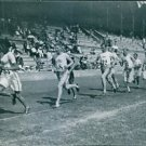 Athletes running in the race track during the Olympics under by Viktor Balck. -