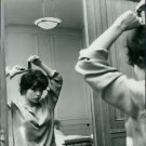 Pascale Petit combing hair in front of mirror - 8x10 photo