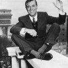Cary Grant sitting on balcony railing. - 8x10 photo