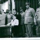 Hussein bin Talal sitting, people standing beside.  - 8x10 photo