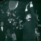 Gilbert Bécaud and Jules Dassin lifting their arms in the air while tray of glas
