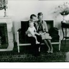 Albert II of Belgium and Queen Paola of Belgium sitting on couch with child.  -