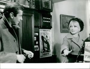 Brigitte Bardot standing with a man. - 8x10 photo