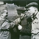 An American sergeant lights the cigarettes of two Russians with whom he works on