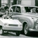 Sheila driving a car and waving.  - 8x10 photo