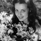 Jeanne Moreau with flowers smiling. - 8x10 photo